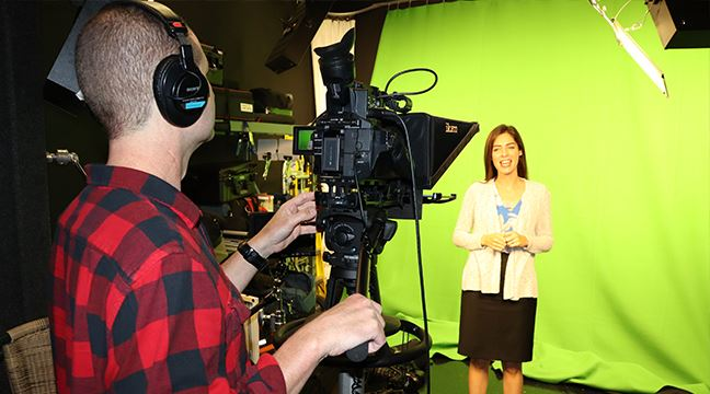 man in flannel shirt operates a camera while a woman stands in a well-lit TV studio