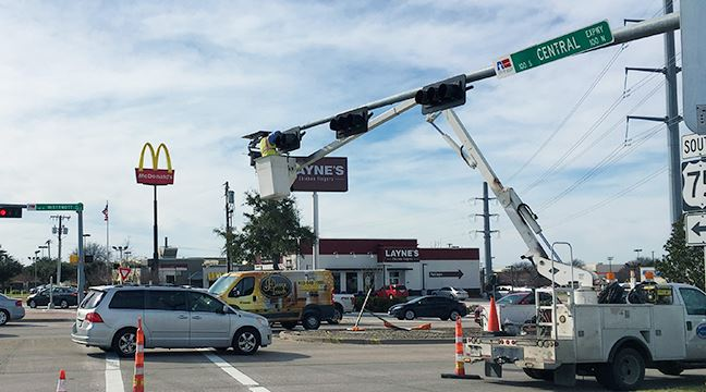 bucket truck extended above traffic signal at US 75 and McDermott in Allen