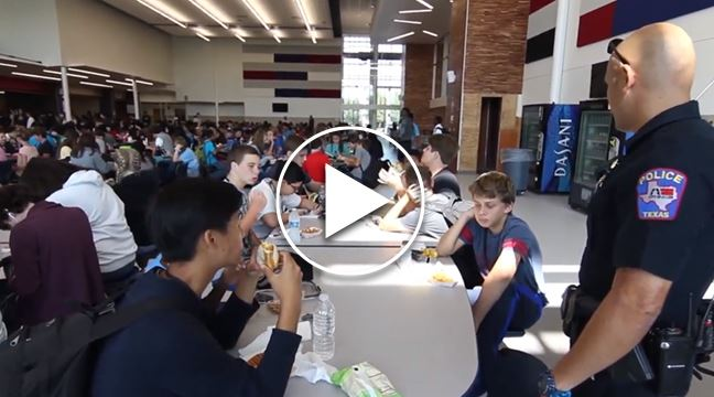 police officer talking to middle school students in cafeteria