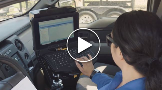 woman inside parked vehicle typing on laptop computer