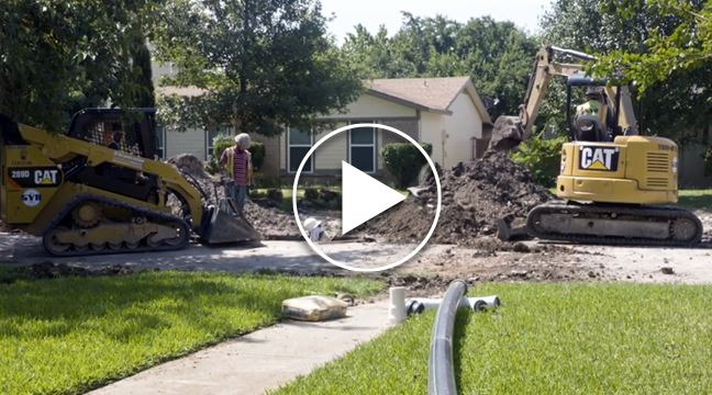 backhoe digging road in residential neighborhood