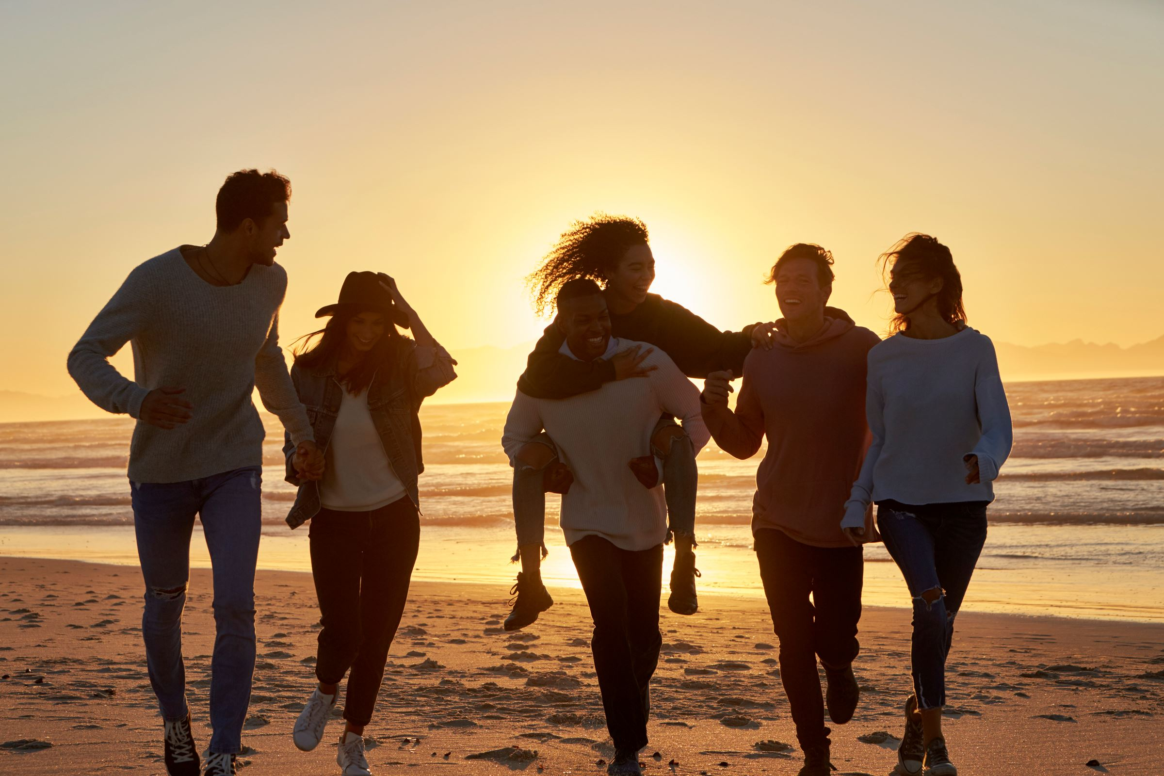 group of friends in casual clothing walking along beach at sunset