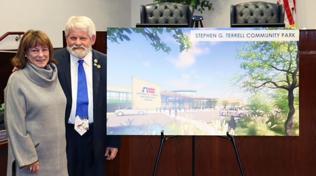 smiling man and woman standing beside easel with artist rendering of new facility