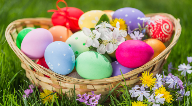 Photo: Basket in the grass with painted eggs.