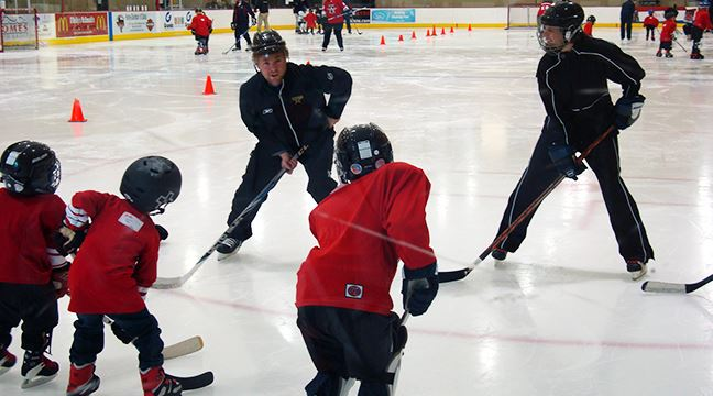 Three young children attending an ice hockey class with two adult instructors