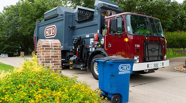 CWD recycling truck arrives at blue recycling bin on a pretty residential street