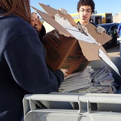 Volunteers dump papers into recycling bin