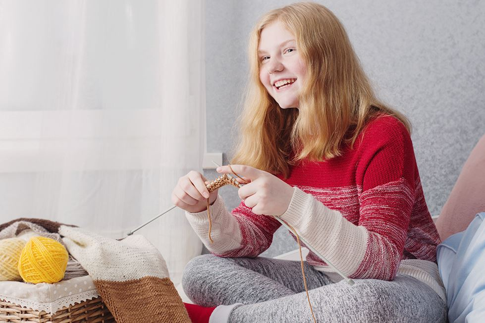 teen girl with knitting needles and yarn
