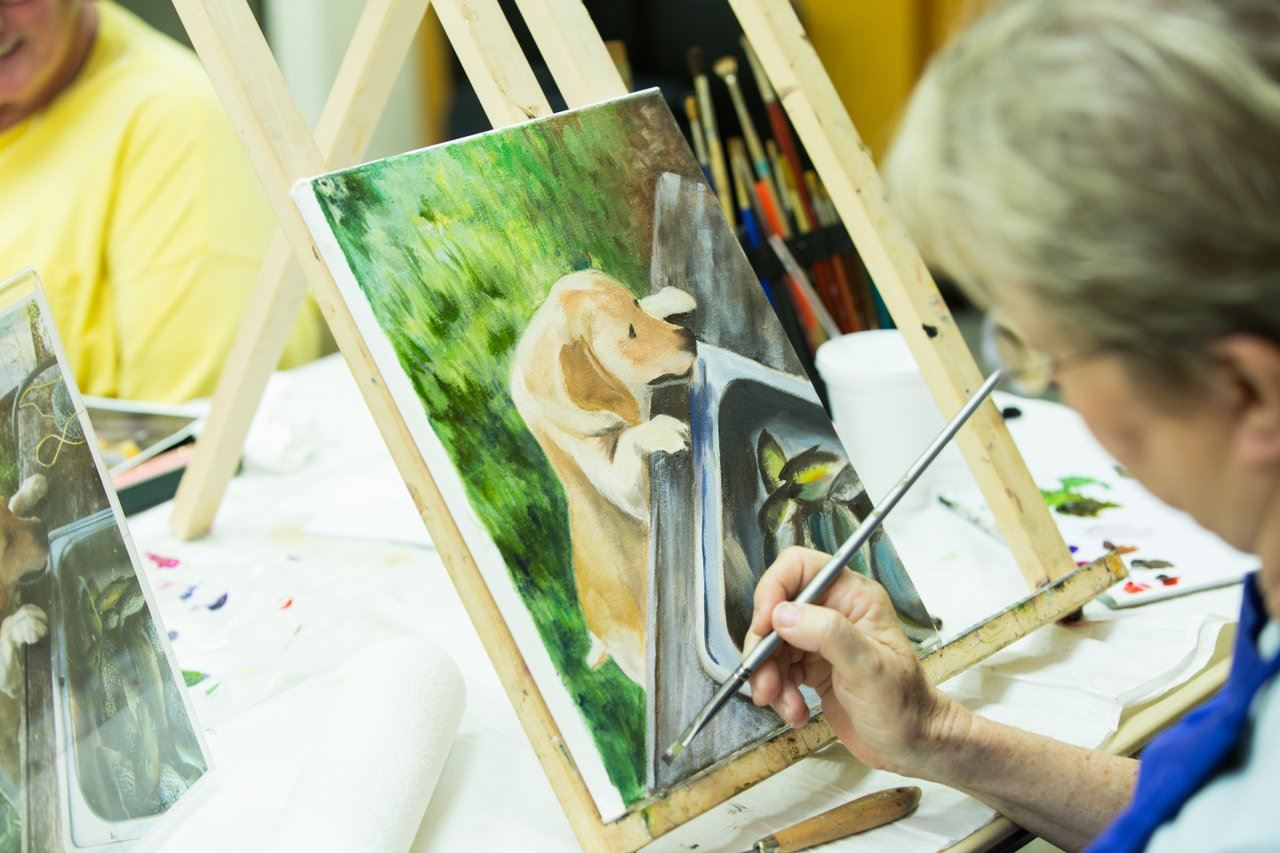 woman works on a fine art painting.
