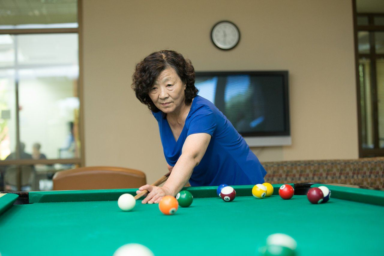 Woman plays billiards.