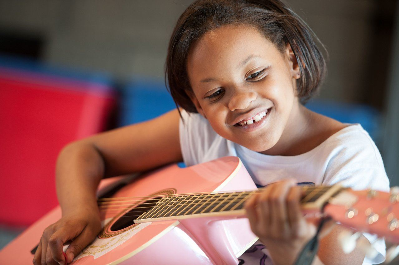 young girl smiles while playing a guitar