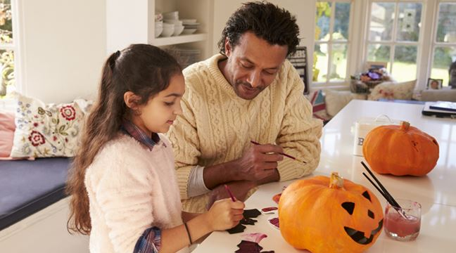 child decorating pumpkin with dad