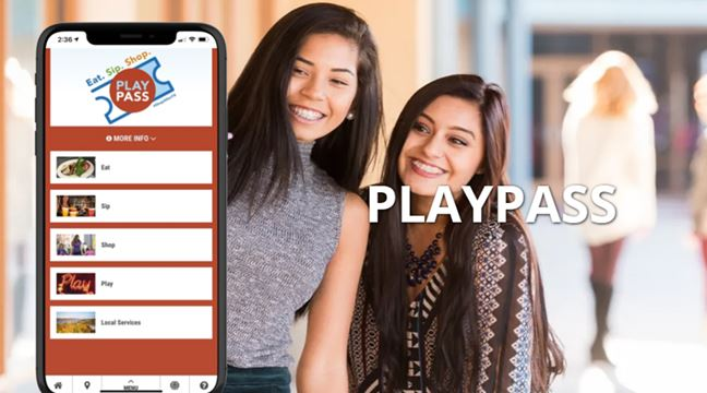 girls posing for photo and mobile phone with the PlayPass app displayed