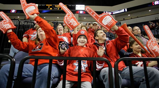 Allen Americans fans with foam fingers celebrating in the stands