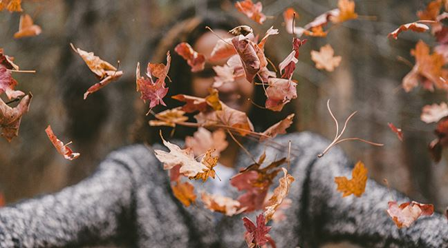 Woman cheerfully tossing fall leaves into the air