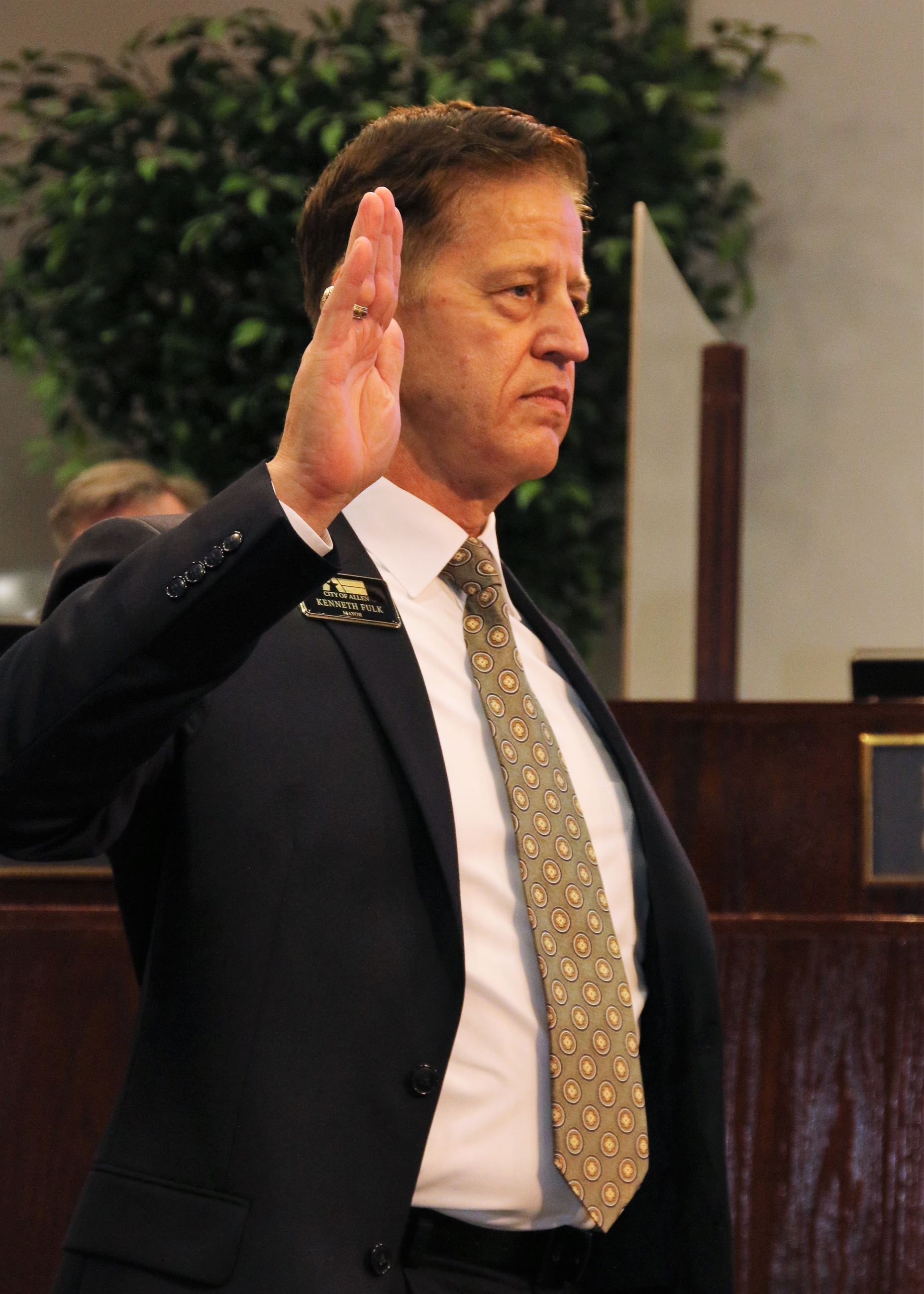 Mayor Ken Fulk holds right hand in the air while sworn in as Allen mayor