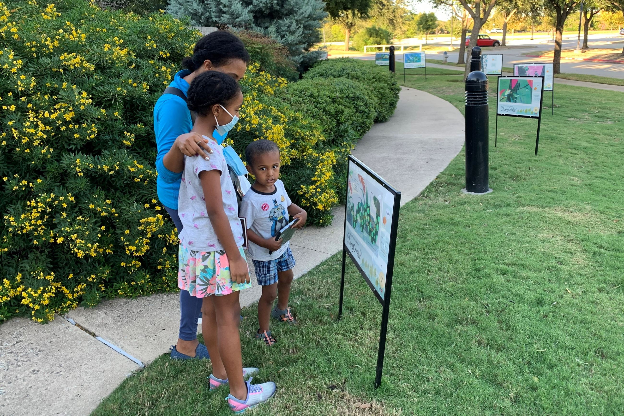 Family looking at one of the StoryWalk signs outside