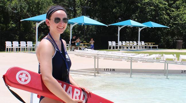 Female lifeguard standing near an outdoor swimming pool