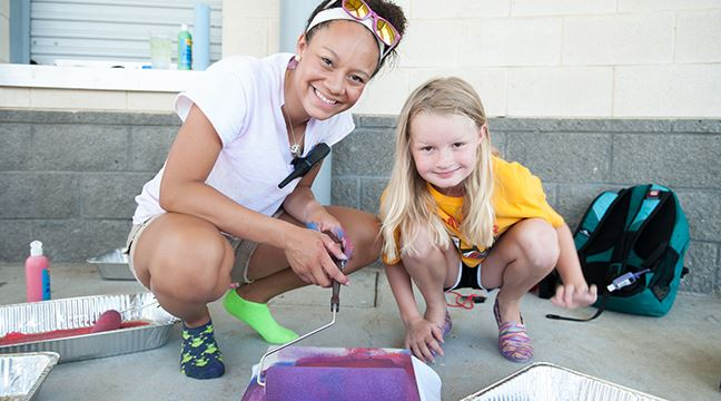 Camp counselor painting a project with a young student