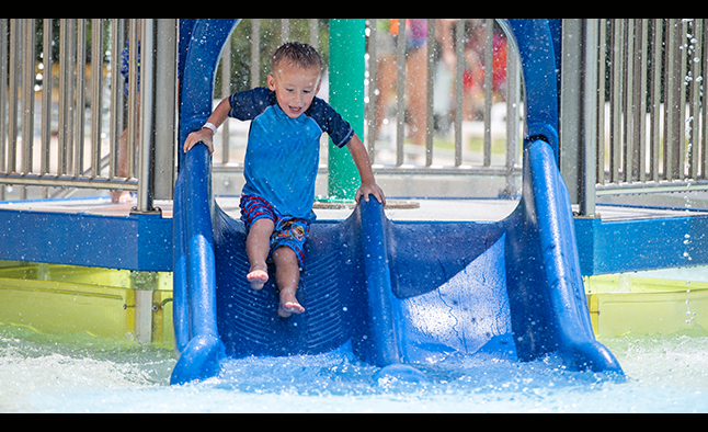 Young boy sliding down a water slide at Ford Pool