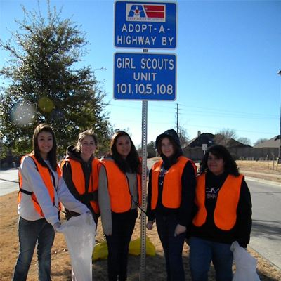 teenage girls standing by road sign