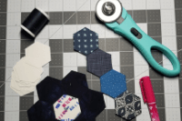 Photo: paper piecing hexagons, dark blue spool of thread, a rotary cutter, a glue pen, and paper pie